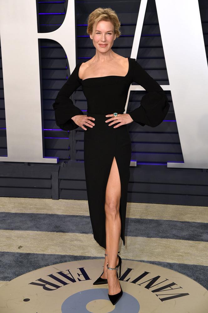 <p> Renée Zellweger diện váy midi đen vừa vặn với thiết kế cổ vuông, tay áo phồng và thân váy xẻ đùi cao gợi cảm.</p>