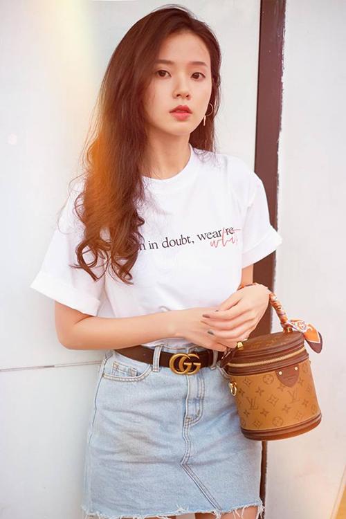Midu trẻ trung khi diện áo phông trắng với váy jeans, kết hợp thắt lưng Gucci và túi xách Louis Vuitton.