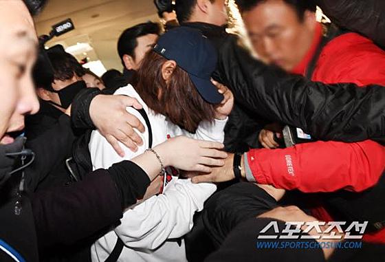 Jung Joon Young được vệ sĩhộ tống, liên tục cúi mặt nhưng vẫn bị chắn kín lối đi. Nam ca sĩ không có bất kỳ lời phát biểu nào.