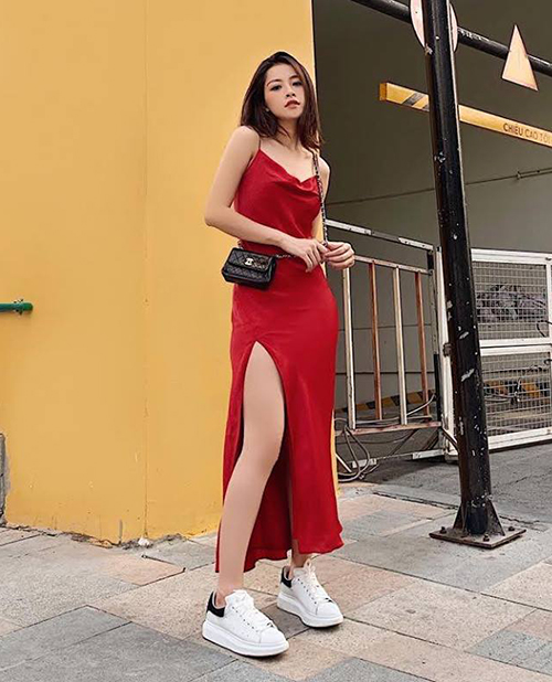 Chi Pu có khả năng biến chiếc váy hai dây lụa đỏ gợi cảm trở nên đầy cá tính bằng cách kết hợp cùng sneakers và belt bag Chanel.