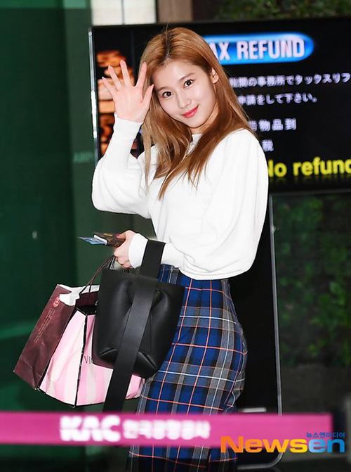 Sana mix áo trắng, chân váy kẻ đậm chất nữ sinh. Ngôi sao nhà JYP được khen ngợi vì vẻ tươi tắn, luôn thân thiện ở sân bay.