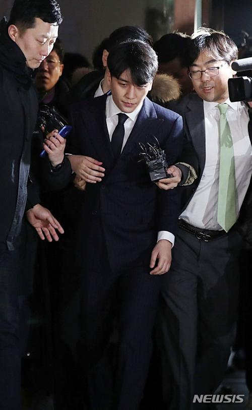 Seung Ri và luật sư Son (cà vạt xanh) rời khỏi Sở cảnh sát Seoul ngày 15/3 sau 16 giờ thẩm vấn.