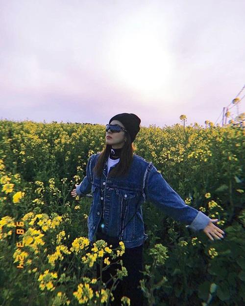 Dara đeo kính đen tạo dáng ngầu giữa đồng hoa cải lãng mạn.