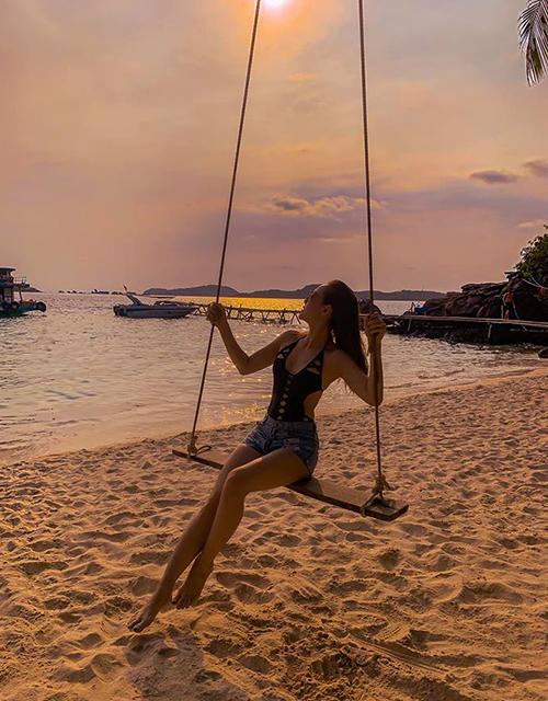 Ngồi xích đu trên bãi biển lúc hoàng hôn, Minh Hằng khoe được đường cong đồng hồ cát.