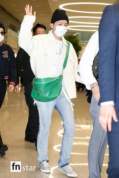 J-Hope đội mũ beanie, đeo túi xách màu xanh lá cây làm điểm nhấn.