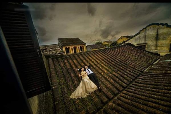 Một cặp đôi chụp ảnh trên mái nhà cổ Hội An.