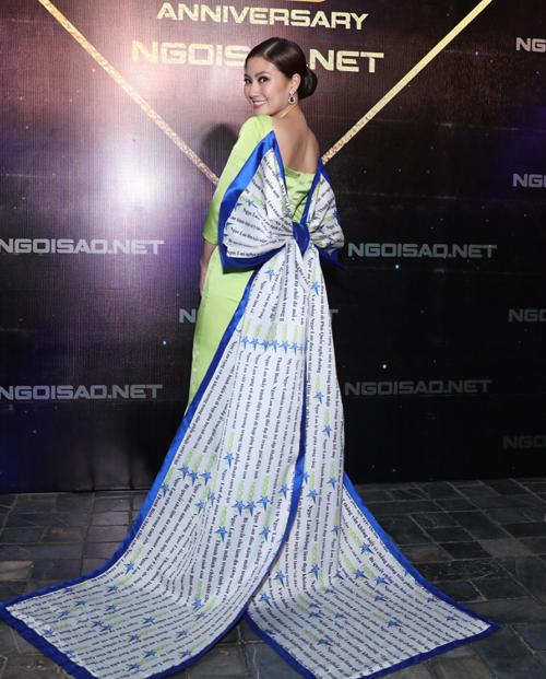 Ngọc Lan diện bộ áo dài xanh đẹp mắt, phía sau là chiếc nơ khổng lồ in logo của báo.