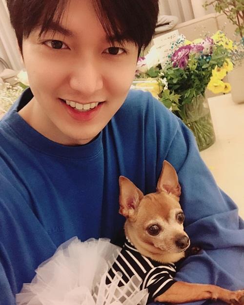 Lee Min Ho ôm cún cưng cười rạng rỡ khoe hoa và quà fan gửi tặng nhân dịp anh chàng xuất ngũ. Tài tử The Heirs bị nhận xét mặt tròn trông thấy.
