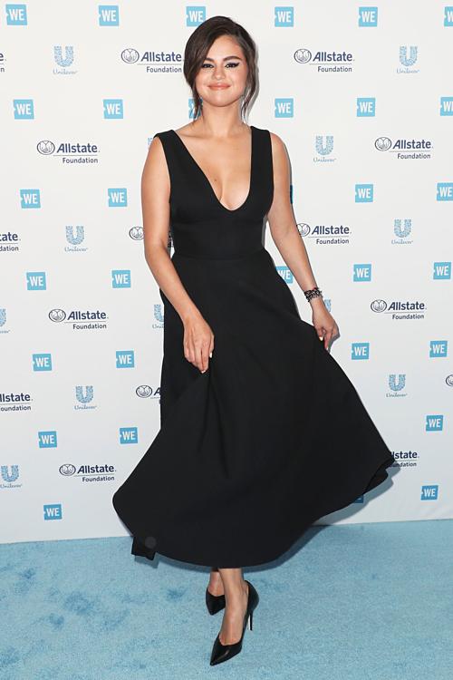 Selena diện váy Dior xẻ ngực, khoe đường cong nóng bỏng. Người đẹp tự tin mỉm cười trước ống kính máy ảnh.