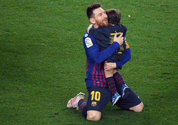 Messi quỳ rạp xuống sân ôm con trai vào lòng.
