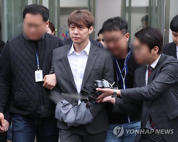 Park Yoo Chun bị còng tay, áp giải về đồn. Cảnh sát xin lệnh bắt giữ trướcdấu hiệu bỏ trốn của nam ca sĩ.