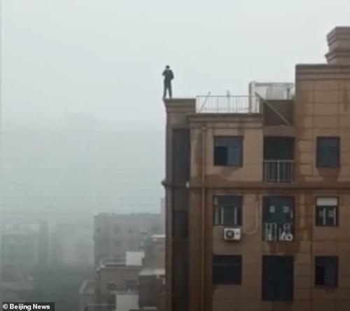 Người thanh niên đứng trên sân thượng để gọi điện.
