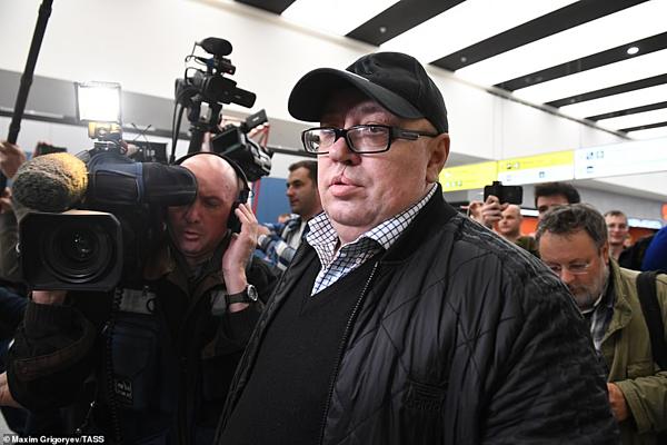 Ông Dmitry Khlebushkin mang theo hành lý rời khỏi máy bay bốc cháy, có mặt tại sân bay. Ảnh: TASS.