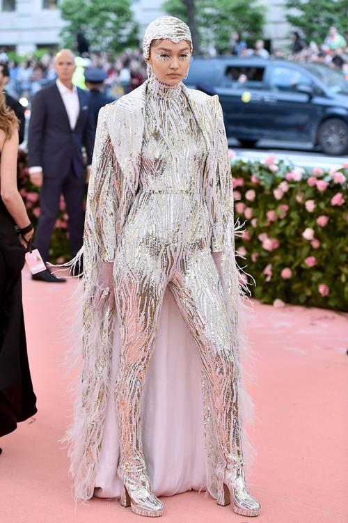 Gigi Hadid kín đáo bất ngờ trên thảm đỏ với bộ bodysuit kín mít từ đầu đến chân của Michael Kors. Trang phục đi kèm áo choàng tăng độ lộng lẫy.