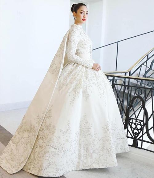 Trên thảm đỏ LHP Cannes ngày thứ sáu, Min Pechaya diện trang phục lộng lẫy kiểu hoàng gia. Bộ đầm phồng với lớp áo choàng của người đẹp thậm chí còn được ví như váy cưới. Đây là thiết kế nằm trong bộ sưu tập Haute Couture Xuân 2019 của thương hiệu cao cấp Ashi.