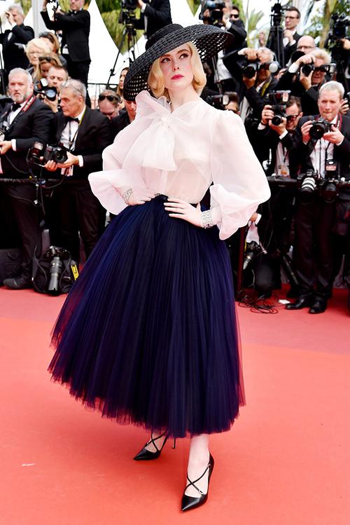 Xuất hiện trên thảm đỏ LHP Cannes 2019 ngày thứ tám, nữ giám khảo trẻ nhất Elle Fanning diện phong cách tiểu thư cổ điển. Cô mix sơ mi trắng thắt nơ với chân váy đen bồng bềnh, kết hợp chiếc mũ cói rộng vành ấn tượng.