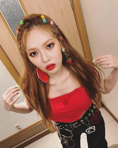 Hyun Ah mặc áo hai dây hình trái tim đỏ rực quyến rũ. Cô nàng đeo cả loạt phụ kiện đủ kiểu trông khá rối mắt.