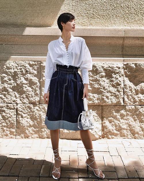 Khánh Linh mang đến set đồ thú vị với sự kết hợp giữa sơ mi trắng và chân váy denim cùng đôi sandals buộc dây đậm chất hè.