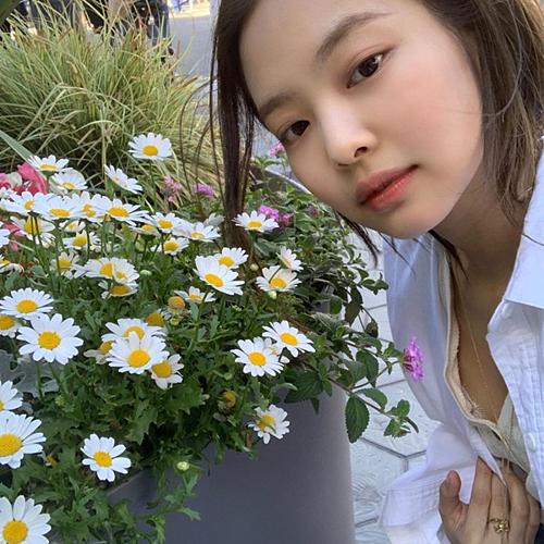 Jennie mặt tròn đáng yêu, thích thú chụp tự sướng với hoa.