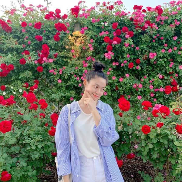 Seol Hyun mặc giản dị, búi tóc củ hành dễ thương tạo dáng trước bức tường hoa.
