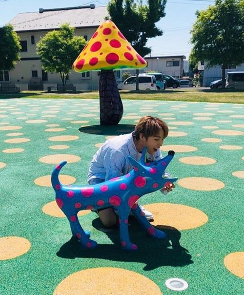 Ha Sung Woon nghịch ngợm bắt chước chú chó đồ chơi há miệng tạo dáng.