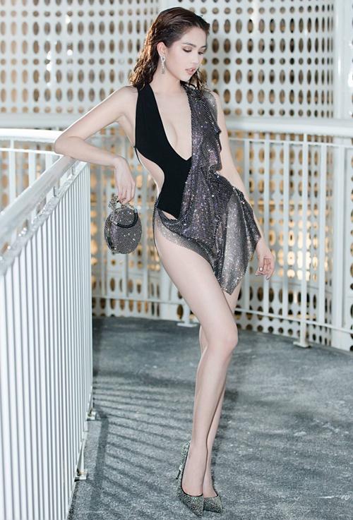 Tối 2/6, Ngọc Trinh tham dự show diễn của NTK Đỗ Long. Bất chấp chỉ trích sau bộ cánh gây tranh cãi tại Cannes 2019, Ngọc Trinhdiện một thiết kế như bikini quấn thêm một lớp khăn mỏng trên thảm đỏ. Thiết kế của Đỗ Long giúp chân dài Trà Vinh khoe tối đa lợi thế vóc dáng, làn da trắng. Cô kết hợp bộ cánh mặc như không cùng phụ kiện ánh bạc metallic.