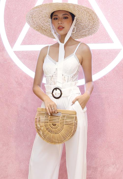 Đồng Ánh Quỳnh diện áo hai dây chất liệu ren xuyên thấu gợi cảm. Cô mix trang phục cùng mũ cói vành rộng và túi chất liệu tre nứa.
