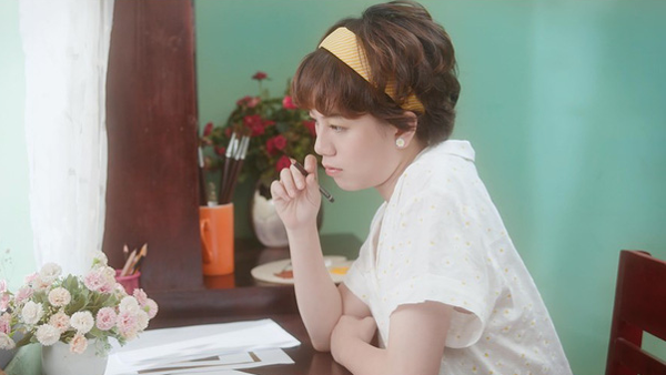 Trong một phân cảnh mới của Về nhà đi con được chia sẻ, Ánh Dương xuất hiện với hình ảnh mơ màng khi đang ngồi viết thư. Cô nàng có biệt danh tomboyloichoi thay đổi khó nhận ra khi diện váy hoa tông xuyệt tông với bông tai. Mái tóc rối bù được chải gọn gàng, điểm nhấn là chiếc băng đô vàng đậm chất vintage.