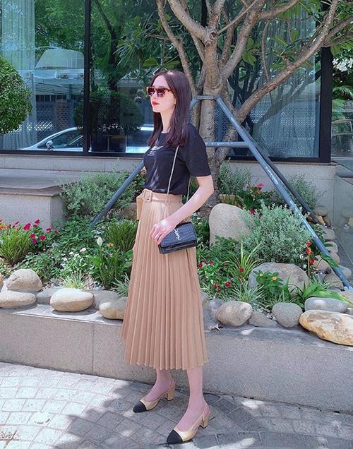 Chân váy xếp ly là lựa chọn tinh tế giúp Thu Thảo che vóc dáng gầy guộc. Túi YSL, giày Chanel hoàn thiện phong cách cổ điển của Hoa hậu.