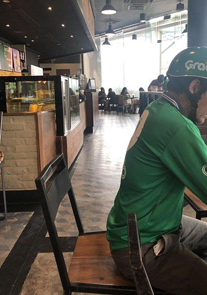 Bức ảnh chụp người tài xế Grab ngồi đợi tại cửa hàng Starbuck do vị CEO Nhật chụp.