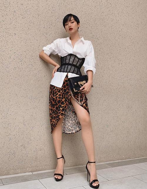 Khánh Linh có khả năng chinh phục những set đồ khó mặc, ví dụ như corset lưới diện bên ngoài sơ mi, kết hợp chân váy da beo.