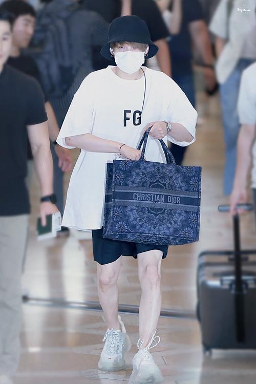 Suga có làn da trắng sáng. Anh chàng mix T-shirt Off White, quần short cùng mũi bucket vàtúi xách Christion Dior sành điệu.