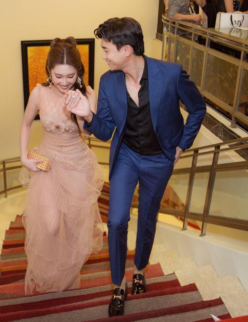 Tối 5/7, Thúy Ngân và Quốc Trường sóng đôi dự show thời trang tại Hà Nội. Thấy Thúy Ngân diện váy dài chấm đất, Quốc Trường ga lăng giúp bạn diễn lên cầu thang.