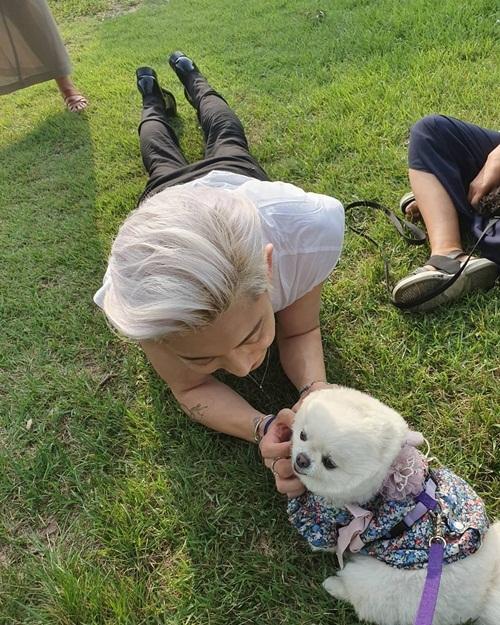 Chan Yeol nằm lăn ra bãi cỏ để cưng nựng cún yêu.