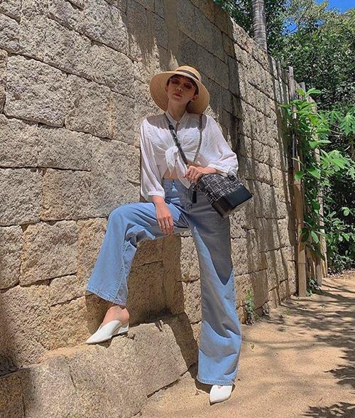 Tóc Tiên chinh phục mốt quần jeans ống thụng mốt năm nay bằng cách mix cùng sơ mi trắng buộc vạt.