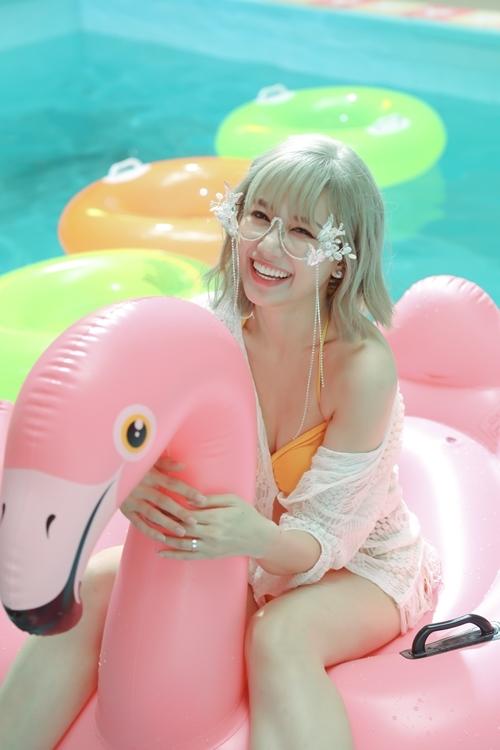 Bộ bikini sắc cam nổi bật mix cùng áo choàng ren cùng phụ kiến kính mát với hình ảnh bướm cách điệu càng làm tăng sự quyến rũ của nữ ca sĩ.