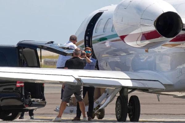 Hoàng tử Anh, Harry lên máy bay sau vợ, anh đội mũ lưỡi trai xám.
