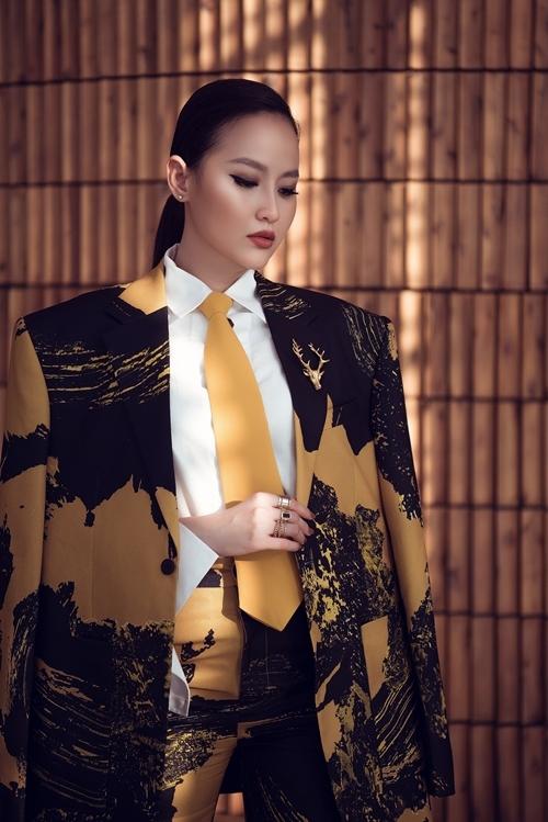 Bộ suit họa tiết trừu tượng được Khánh Ngân phối cùng áo sơ mi trắng và cà vạt tiệp màu. Cô trang điểm sắc sảo, vuốt tóc ngược về phía sau tạo sự mạnh mẽ cho diện mạo.
