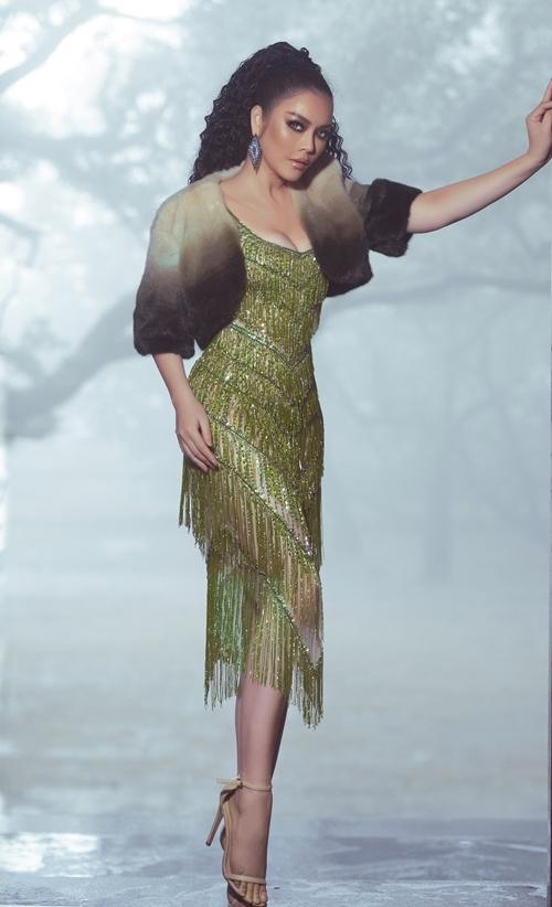 Váy hai dâyđính đá tua rua được Lý Nhã Kỳ phối hợp cùng áo khoác lông mỏng.