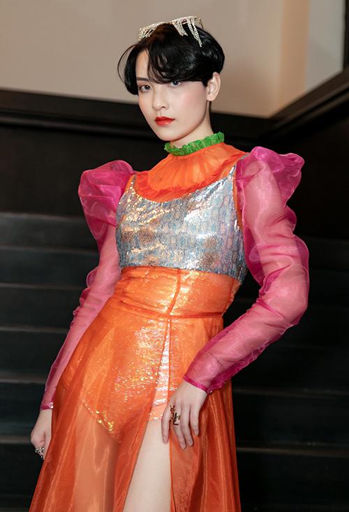Hot girl vận đồ layer sặc sỡ, phía trong là bodysuit khoe chân, phía ngoài là lớp tà xẻ cao đến hông. Cô kết hợp cùng cách trang điểm môi đỏ nổi bật không kém.