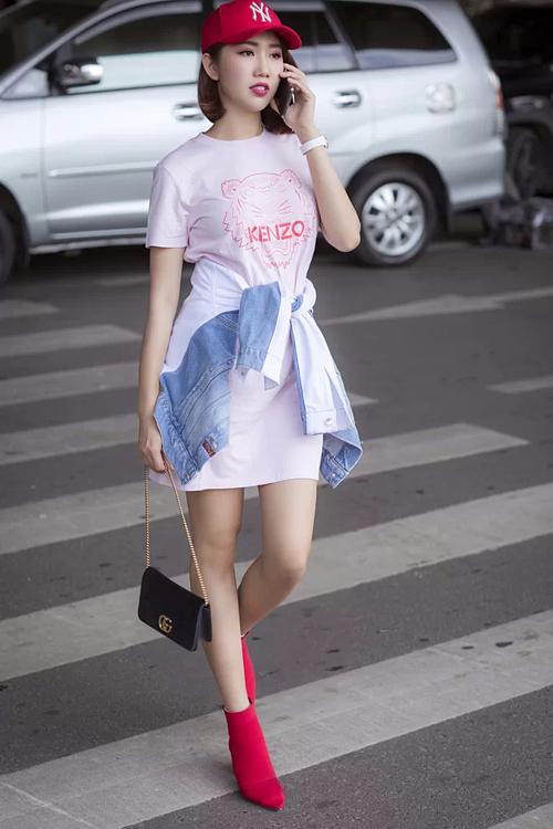 Thúy Ngân tăng phong cách cho váy liền dáng suông của Kenzo bằng áo khoác denim buộc ngang eo.