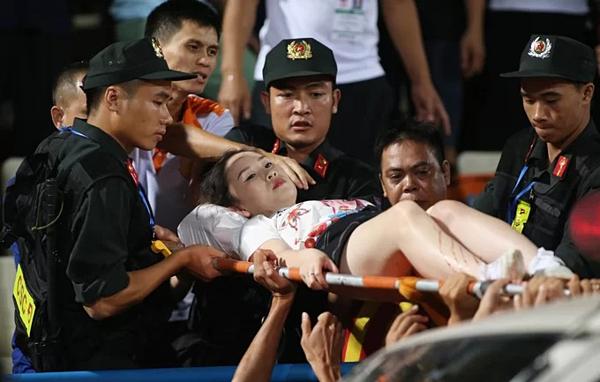 Lực lượng an ninh và bác sĩ chuyển CĐV đi bệnh viện cấp cứu. Ảnh: Lâm Thỏa.
