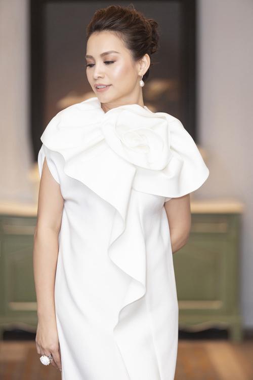 Hoa hậu Việt Nam 1998 Ngọc Khánh trẻ trung với chiếc đầm trắng có chi tiết hoa, dún bèo to bản. Chị kết hợp trang phục cùng giày dây quai mảnh, hoa tai ngọc trang giúp vẻ ngoài thêm cuốn hút.
