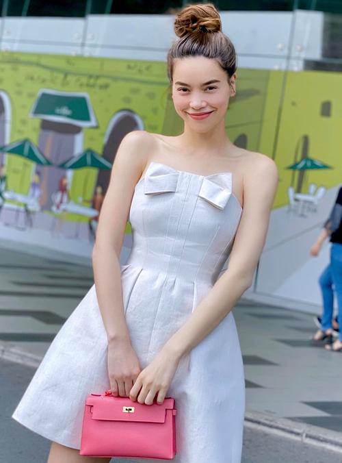 Chiếc váy cúp ngực màu trắng mang đến cho Hà Hồ vẻ ngoài như búp bê. Nữ ca sĩ trông càng trẻ trung khi xách túi Hermes hồng giá vài trăm triệu đồng.