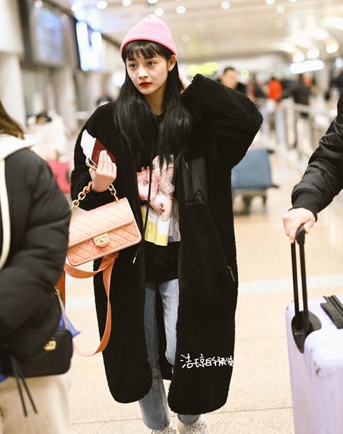 Thần tượng Trung Quốc, Chu Khiết Quỳnh (Kyul Kyung) (Pristin) diện item màu đen kết hợp với áo khoác hợp tông, set đồ nổi bật với túi xách và mũ len hồng.