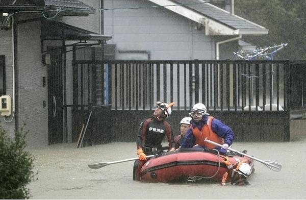 Lực lượng cứu hộ dùng xuồng đưa người bị mắc kẹt tới nơi an toàn.