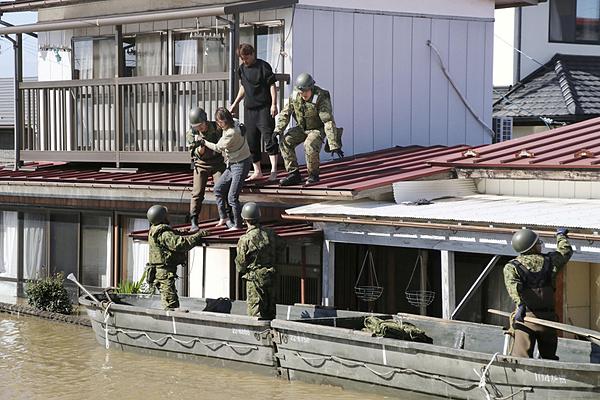 Lực lượng cứu hộ giải cứu người mắc kẹt sau cơn bão Haginbis. Ảnh: Reuters.