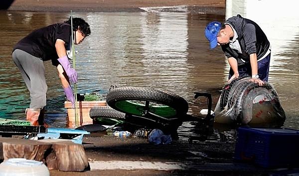 Người dân bắt đầu dọn dẹp tại khu dân cư bị ngập lụt ở Kawasaki. Ảnh: Reuters.