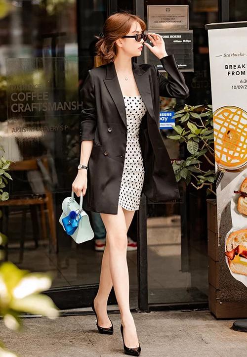 Ngọc Trinh kết hợp blazer đen và váy chấm bi. Trên tay cô nàng là chiếc túi mới toanh của Delvaux, giá hơn 3.000 USD.