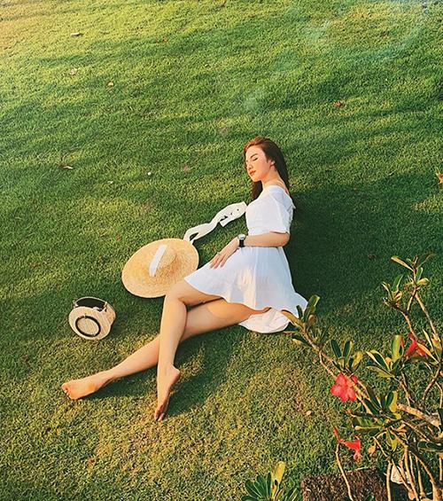 Hạnh Sino nằm dài khoe dáng trên bãi cỏ.